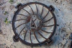 Einsteigeloch mit rostiger Metallabdeckung im sandigen Boden Stockbild