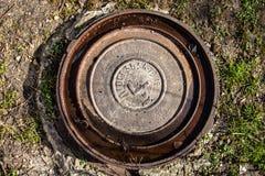 Einsteigeloch mit rostiger Metallabdeckung und -wasser in seinen Nuten Stockfoto