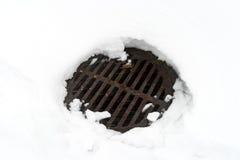 Einsteigelochabdeckung im weißen Schnee Lizenzfreies Stockbild