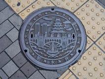 Einsteigelochabflussabdeckung auf der Straße in Osaka, Japan Lizenzfreie Stockbilder