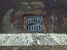 Einsteigelochabwasserkanal in einer ruinierten Straße Stockbild