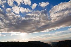 Einstellung Sun, der durch einen Block der Wolken bricht Stockfotografie