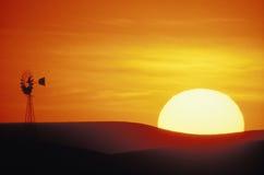 Einstellungssonne mit Windmühle lizenzfreies stockfoto