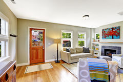 Einstiegstür und ein roter moderner Stuhl Wohnzimmer mit Kamin und bequemem Sofa Lizenzfreie Stockfotos