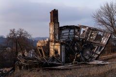 Einsturz, verlassenes Haus auf unfruchtbarer Straße bei Sonnenuntergang Stockbild