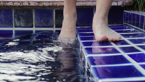 Eintauchen der Zehe im Swimmingpool stock video footage