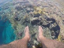 Eintauchen von Füßen im Meerwasser vom Pier Stockfotos