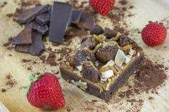 Einteiler des Schokoladenkuchens mit Schokolade und einigen Erdbeeren Stockfotografie