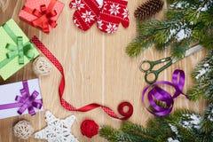 Einwickelnde Weihnachtsgeschenke und Schneetannenbaum über Holztisch Stockbild