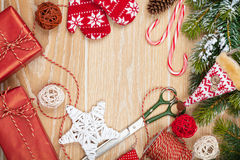 Einwickelnde Weihnachtsgeschenke und Schneetannenbaum über Holztisch Lizenzfreie Stockbilder