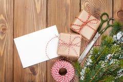Einwickelnde Weihnachtsgeschenke und Schneetannenbaum Lizenzfreie Stockfotografie