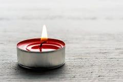 Einzelne brennende rote tealight Kerze Stockfotos