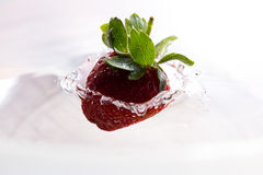 Einzelne Erdbeere, die auf Wasser fällt Lizenzfreie Stockfotografie