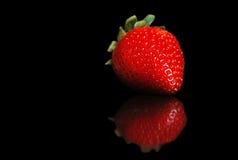 Einzelne Erdbeere mit Reflexion auf Schwarzem Lizenzfreies Stockfoto