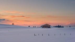 Einzelne Hütte bei Sonnenuntergang im Winter an der schneebedeckten Wiese Lizenzfreie Stockbilder