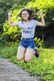 Einzelne junge modische energische asiatische Dame mit den langen Haarschauspielen, die kurzen Denimbaumwollstoff tragen, springe Lizenzfreie Stockbilder