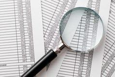 Einzelne Lupe auf Geschäftsberichte Lizenzfreies Stockbild
