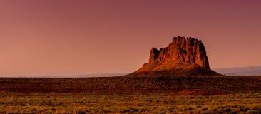 Einzelne Rock-MESA-Felsformation in der Wüste bei Sonnenuntergang stockfotos