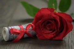 Einzelne rote Rosen und Bündel Dollar Stockbild