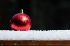 Einzelne rote Verzierung auf Schneedunkelheitshintergrund Stockfoto