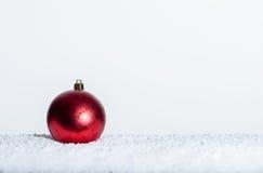 Einzelne rote Weihnachtsverzierung auf Schnee Stockbild