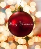 Einzelne rote Weihnachtsverzierung, die vor Lichtern hängt Stockfotos