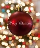 Einzelne rote Weihnachtsverzierung, die vor Lichtern hängt Stockfoto