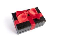 Einzelne schwarze Geschenkbox mit rotem Band stockfotografie