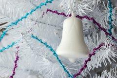 Einzelne weiße dekorative Glasglocke auf weißem Weihnachtsbaum Lizenzfreie Stockfotografie