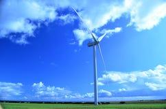 Einzelne Windkraftanlage auf einem grünen Gebiet gegen einen blauen Himmel lizenzfreies stockfoto
