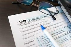 Einzelner Abschluss der Steuererklärungs-Form 1040 oben mit Stift, Gläsern und Laptop Stockbilder