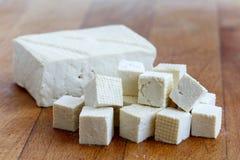 Einzelner Block des weißen Tofus mit geschnittenen Tofuwürfeln auf hölzernem choppin Lizenzfreie Stockfotos