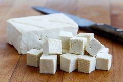Einzelner Block des weißen Tofus mit geschnittenen Tofuwürfeln und rustikalem Messer Stockfotos