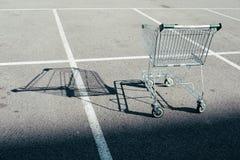 Einzelner Einkaufswagen im Parkplatz stockbild