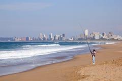 Einzelner Fischer Fishing im Ozean in Durban, Südafrika Lizenzfreies Stockbild
