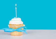 Einzelner kleiner Kuchen mit beleuchteter blauer Kerze Lizenzfreies Stockbild