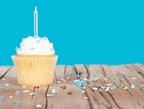 Einzelner kleiner Kuchen mit blauer Kerze und spritzt Stockbild