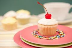 Einzelner kleiner Kuchen mit einer Kirsche auf die Oberseite Stockbild