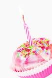 Einzelner kleiner Kuchen mit rosafarbener beleuchteter Kerze Stockbilder
