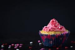 Einzelner kleiner Kuchen und das rosa Bereifen mit zerstreut besprüht auf dunklem Hintergrund Lizenzfreie Stockbilder