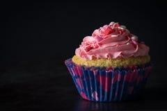 Einzelner kleiner Kuchen und rosa Bereifen auf Tabelle mit dunklem Hintergrund Stockfoto