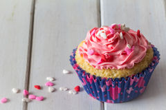 Einzelner kleiner Kuchen und rosa Bereifen auf Tabelle mit Kopien-Raum über Vertikale Lizenzfreie Stockbilder