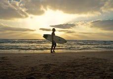 Einzelner männlicher Surfer mit einem Surfbrett gehend auf einen sandigen Strand auf einem bewölkten Sonnenuntergang stockfoto