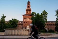 Einzelner Mann auf dem Fahrrad, das allein vor Castello Sforzesc reitet lizenzfreies stockfoto