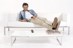 Einzelner Mann auf der Couch Fernsehend Stockfotos