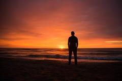 Einzelner Mann, der einen drastischen Sonnenuntergang durch das Meer aufpasst Lizenzfreie Stockbilder