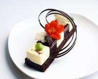 Einzelner Nachtisch mit essbarer Blumen- und Schokoladendekoration auf weißer Platte lizenzfreies stockbild