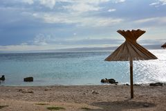 Einzelner Regenschirm auf Seelandschaft stockfoto