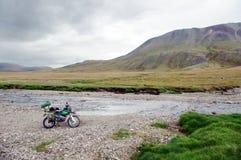 Einzelner Reisender des Motorrades mit den Koffern, die auf Steinbank des Gebirgsflussstromes stehen Lizenzfreies Stockbild