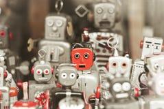 Einzelner Roboter, stehend heraus unter der Masse von Robotern Lizenzfreie Stockfotos